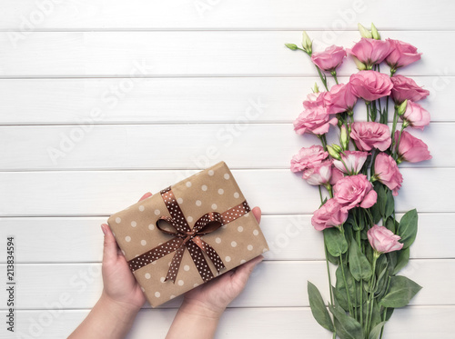 Beautiful pink eustoma flowers and woman hands holds handmade gift box on white wooden background. Copy space, top view, - 213834594