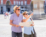 Happy senior couple looking for directions using a map on holidays in a European city