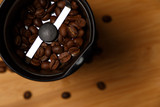 Electric coffee grinder with roasted coffee beans on the kitchen table with blue tabletop. Top view. Close-up - 213847561