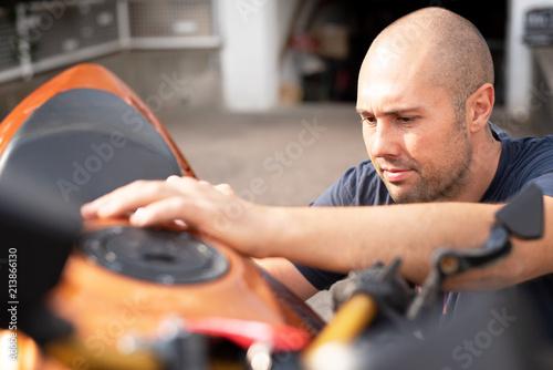 Mann putzt sein Motorrad