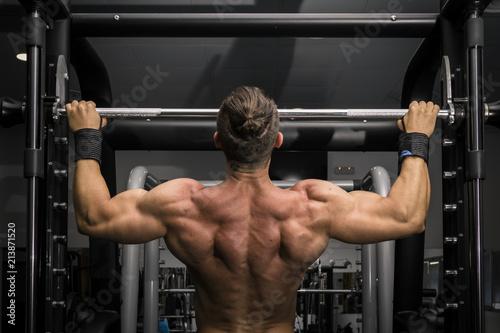 Hombre fuerte con grandes músculos haciendo dominadas en el gimnasio de espaldas. Ponerse en forma.