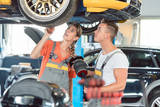 Experienced female auto mechanic checking tires before installing together with her colleague a new air suspension system in a modern automobile repair shop - 213900980