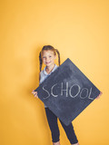 blond girl is standing in front of yellow, orange background and is holding a blackboard with the word school on it - 213907970