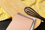 Blank sheet of opened notepad and kitchen utensils on  table with tablecloth, copy space - 213908748