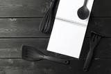 Blank sheet of opened notepad and kitchen utensils on  table with tablecloth, copy space - 213908795