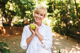 Happy mature woman holding green apple
