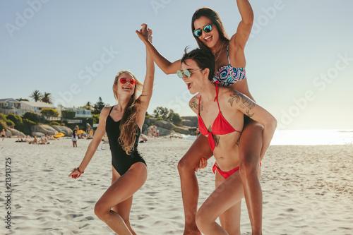 Woman friends sunbathing and having fun at the beach