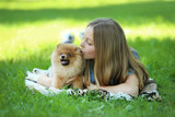 Young girl with pomeranian dog in the park - 213928703