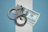 Guatemala flag  with handcuffs and a bundle of dollars. Currency corruption in the country. Financial crimes