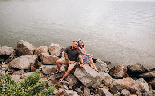 Foto Murales Cute couple in love , sitting on the stones on blue sea background. Young man and woman hugging. Summer day
