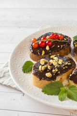 Sandwiches with chocolate paste, pistachio nuts and fresh berries on a plate.