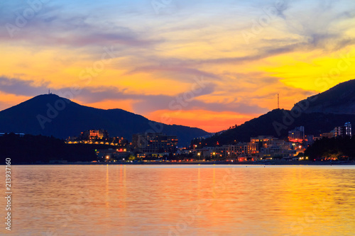 Foto Spatwand Oranje Colorful sunset on Adriatic sea coastline, view to the city in Montenegro, gorgeous seascape