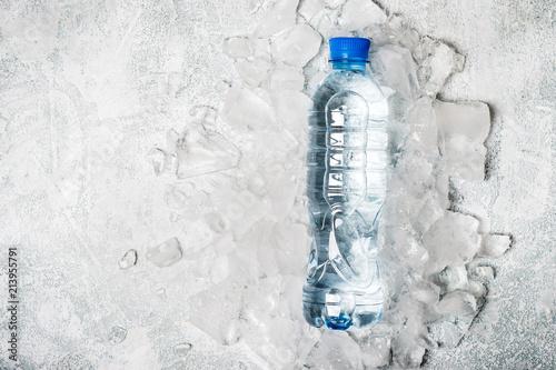 woda w butelce na tle lodu. Koncepcja detox zdrowia