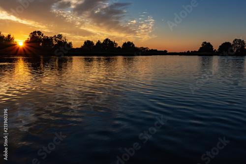 Beautiful sun rays during sunset in lake Zoetermeerse plas - 213960396