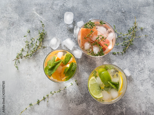 Set summer cold drinks with different citrus in glasses on a gray background. Cocktail with grapefruit, orange, lemon lime, ice and herbs. Refreshing diet drink. Top view. Copy space - 213961760