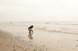 North Sea beach in Denmark at cloudy day. Small girl collecting stones. - 213963528