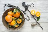 agrumi arance mandarini in piatto bilancia stadera su tavolo legno grezzo bianco