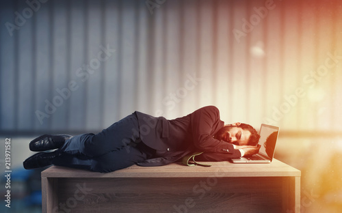Leinwandbild Motiv Businessman sleeping over a desk due to overwork