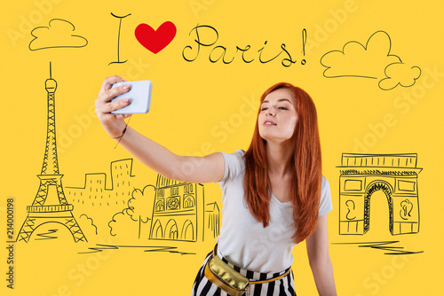 Wall mural Selfie in Paris. Cheerful relaxed young woman smiling and posing while being in Paris and taking a selfie with a help of her modern smartphone