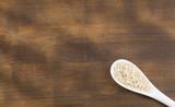 Organic white sesame seeds - Sesamum indicum - Wooden background - 214005724