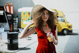 Summer sunny lifestyle portrait of young beautiful woman walking on the street market, wearing cute red trendy dress, drinking tasty smoothie, smiling enjoy her weekends, holiday.