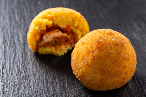 In de dag Palermo Sicilian Arancino, typical fingers food Sicily, Italy. Fried rice balls, meat-based Italian sauce and peas.