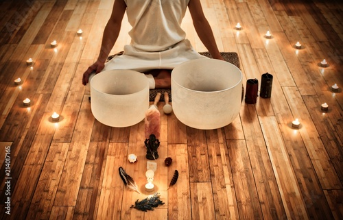 Fototapeta Man sitting in indian behind his two musical crystal bowls, with a display of sacred object and surrounded by candles