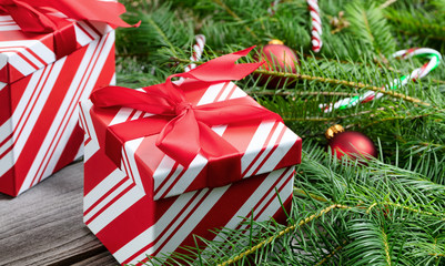 Close up view of a boxed gift with real Christmas tree branches and ornaments in the background
