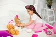 Little cute girl playing with her teddy bears. Lovely little preschooler playing with toys at home sitting on bed in white room.