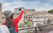 Quadro tourist girl taking a selfie in Rome city. Italy. Colloseum in background