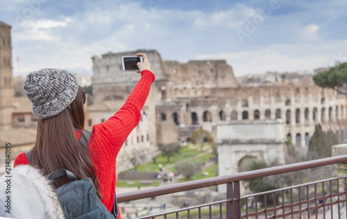 tourist girl taking a selfie in Rome city. Italy. Colloseum in background