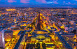 Aerial view of Gare Montparnasse illuminated by blue hour from panoramic Tour Montparnasse. Paris urban cityscape. Parisian style architecture of France in Europe. Night scene.