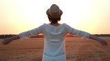 The girl stands on a wheat field and raises his hands up. Silhouette of a woman at sunset. - 214058956