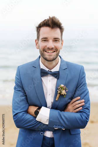 Leinwanddruck Bild Handsome groom at the beach