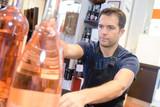 seller installing bottles in his store - 214072117