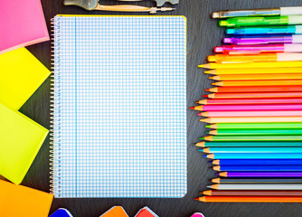 Back to school pencils and pens rainbow and ruled notebook, retro toned
