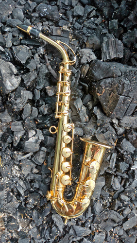 A golden alto saxophone on a background of black coals and burned ebony. Original design or cover for music in the style of jazz, modern - 214074369