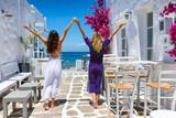 Zwei glückliche Touristinnen genießen ihren Sommerurlaub auf einer typisch griechischen Insel auf den Kykladen, Paros, Griechenland - 214083501