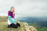 A girl-traveler with multicolored hair sits on the edge of a cliff and looks to the horizon on a background of a rocky plateau - 214099103