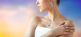 beauty, jewelry, people and luxury concept - beautiful asian woman or bride with earring, finger ring and pendant over pastel background