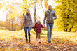 Quadro family, season and people concept - happy mother, father and little daughter walking at autumn park