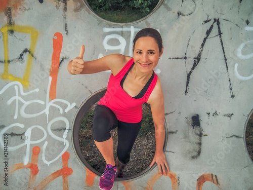 smiling female Fitness Coach in pink sportswear making Thumbs up outdoor with a hipster graffiti background