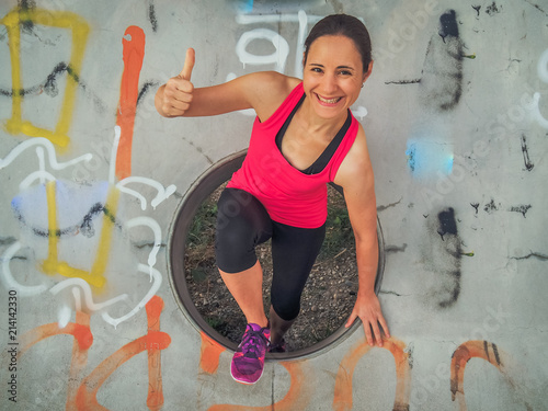 Foto Spatwand Graffiti smiling female Fitness Coach in pink sportswear making Thumbs up outdoor with a hipster graffiti background