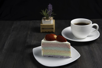 Rainbow crape cake with fruit fresh strawberry on white plate with a cup of hot tea on dark wooden table, isolated black background. © suwanb