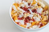 Healthy vegan salad. Mango, tangerine, banana, dried apricot, walnut, coconut flakes, pomegranate in a bowl. Healthy fruit dessert