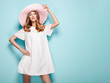 Leinwandbild Motiv Blonde Young Woman in Summer White Dress and Summer Hat. Girl Posing on a Turquoise Background. Hairstyle and Clothing. Fashion Photo