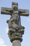 Ancient white stone crucifix with Jesus in blue sky