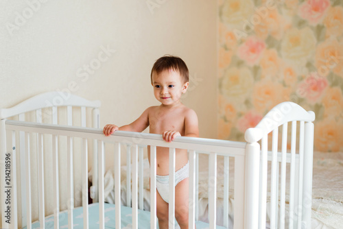 Fototapeta Smiling toddler in white diaper standing in hid child bed. Flower print wallpaper in the background. Happy growing up concept