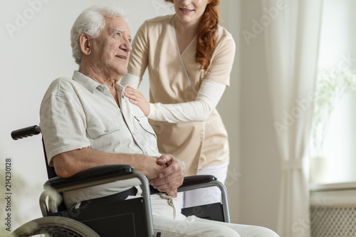 Caregiver supporting sick elderly man in the wheelchair during stay in the hospice