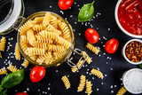 Raw pasta with spices on black stone on wooden background
